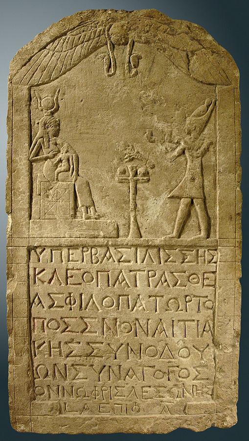 Estela de piedra caliza de Cleopatra vestida como un faraón presentando ofrendas a Isis