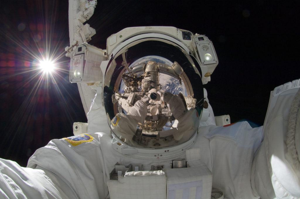 Expedición 32 a la Estación Espacial Internacional (5 sept. 2012) - El astronauta de la Agencia de Exploración Aeroespacial de Japón Aki Hoshide, ingeniero de vuelo de la Expedición 32, utiliza una cámara fotográfica digital para autoretratarse. Durante la caminata espacial de seis horas y 28 minutos, Hoshide y la astronauta de la NASA Sunita Williams (visible en los reflejos de la visera del casco de Hoshide), ingeniero de vuelo, completaron la instalación de una Unidad de Conmutación de Autobús Principal (MBSU) e instalaron una cámara en el brazo robótico de la Estación Espacial Internacional, Canadarm2. El sol brillante es visible a la izquierda. - Créditos:  Créditos: NASA [dominio público], vía spaceflight.nasa.gov