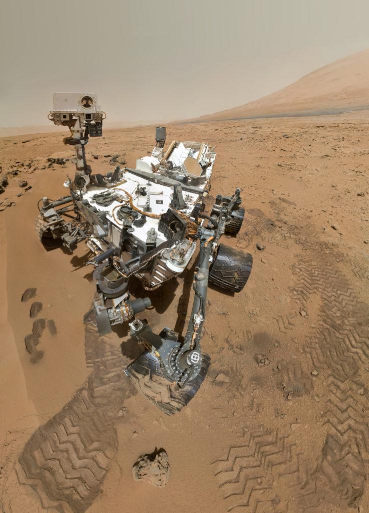 Día marciano 84 de exploración (31 de octubre de 2012), el rover Curiosity de la NASA utilizó el Mars Hand Lens Imager (MAHLI) para capturar este conjunto de 55 imágenes de alta resolución, que fueron unidas para crear este selfie. Autorretratos como éste documentan el estado del rover y permiten a los ingenieros de la misión seguir los cambios a lo largo del tiempo, como la acumulación de polvo y el desgaste de las ruedas. Debido a su ubicación en el extremo del brazo robótico, sólo MAHLI (entre las 17 cámaras del rover) es capaz de visualizar algunas partes de la embarcación, incluyendo las ruedas laterales de babor. - Créditos: NASA/JPL-Caltech/Malin Space Science Systems Trabajo derivado que incluye clasificación, corrección de distorsión, ajustes locales menores y renderizado a partir de archivos tiff: Julian Herzog [Dominio público], vía Wikimedia Commons