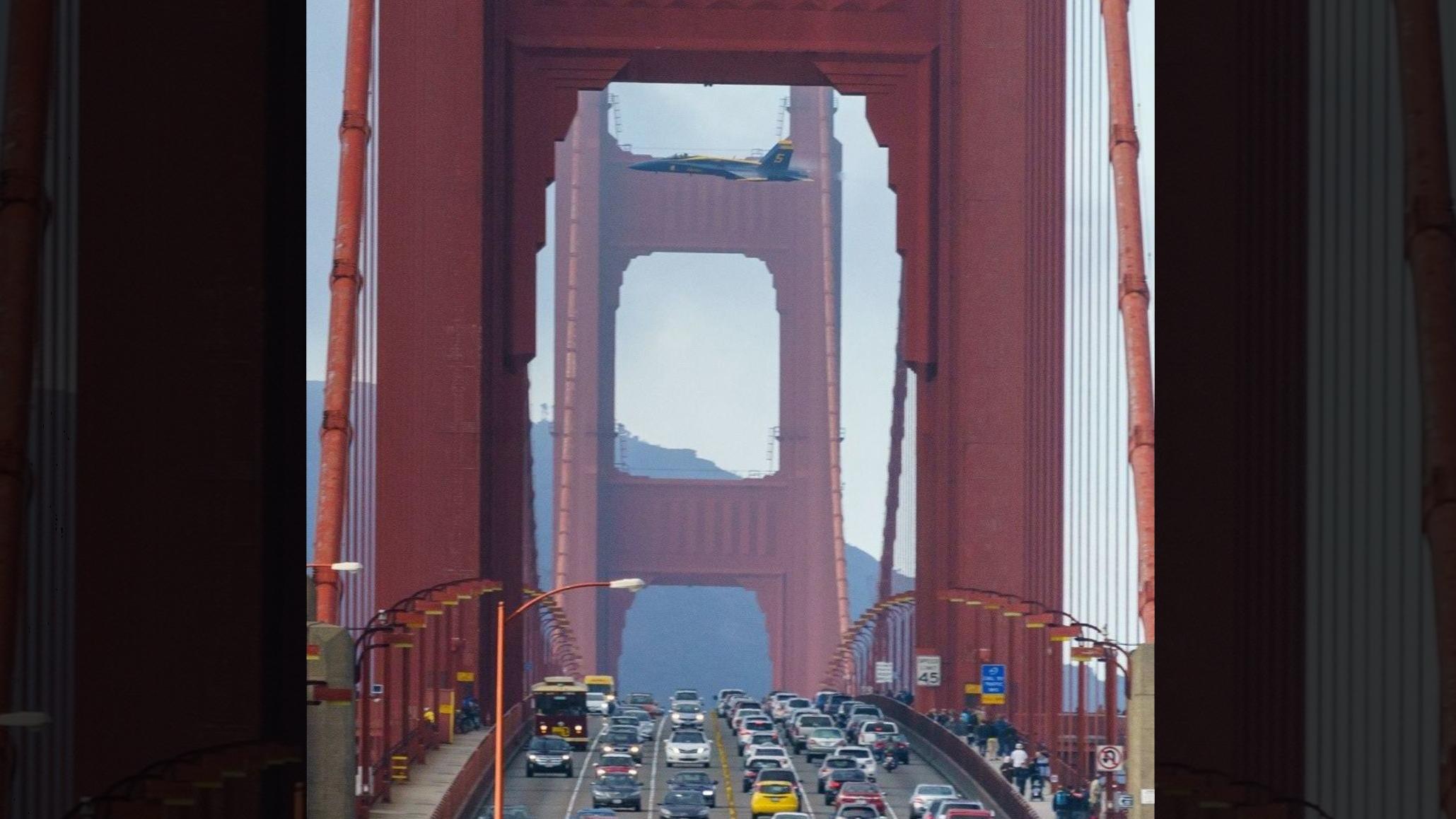 F-18 en vuelo de demostración entre las torres del Golden Gate, mientras circulan por él coches y peatones
